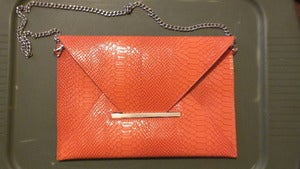 Image of Orange snake print clutch
