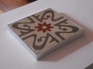 Image of Oxblood flower on grey and creme background trivet