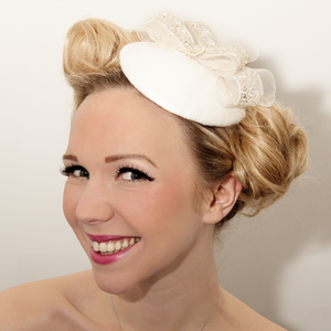 Image of Bridal fascinator, decorated with embellished bows and a solid silver good luck charm.
