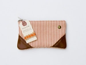 Image of --SOLD OUT-- a small coral + sand zipper pouch with leather corners and a METAL zipper