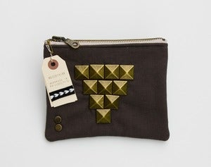 Image of a large zipper pouch in dark grey with oversized pyramid studs + a metal zipper