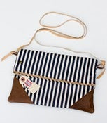 Image of a foldover clutch in navy + white stripe with a removable strap!